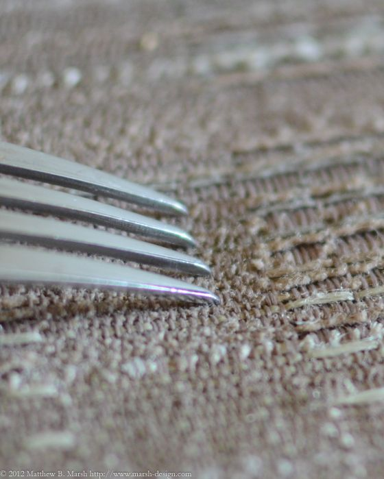 AF fine tune calibration: a fork against a textured fabric background
